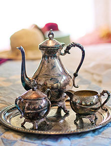 Antique tea pot and cups on bed