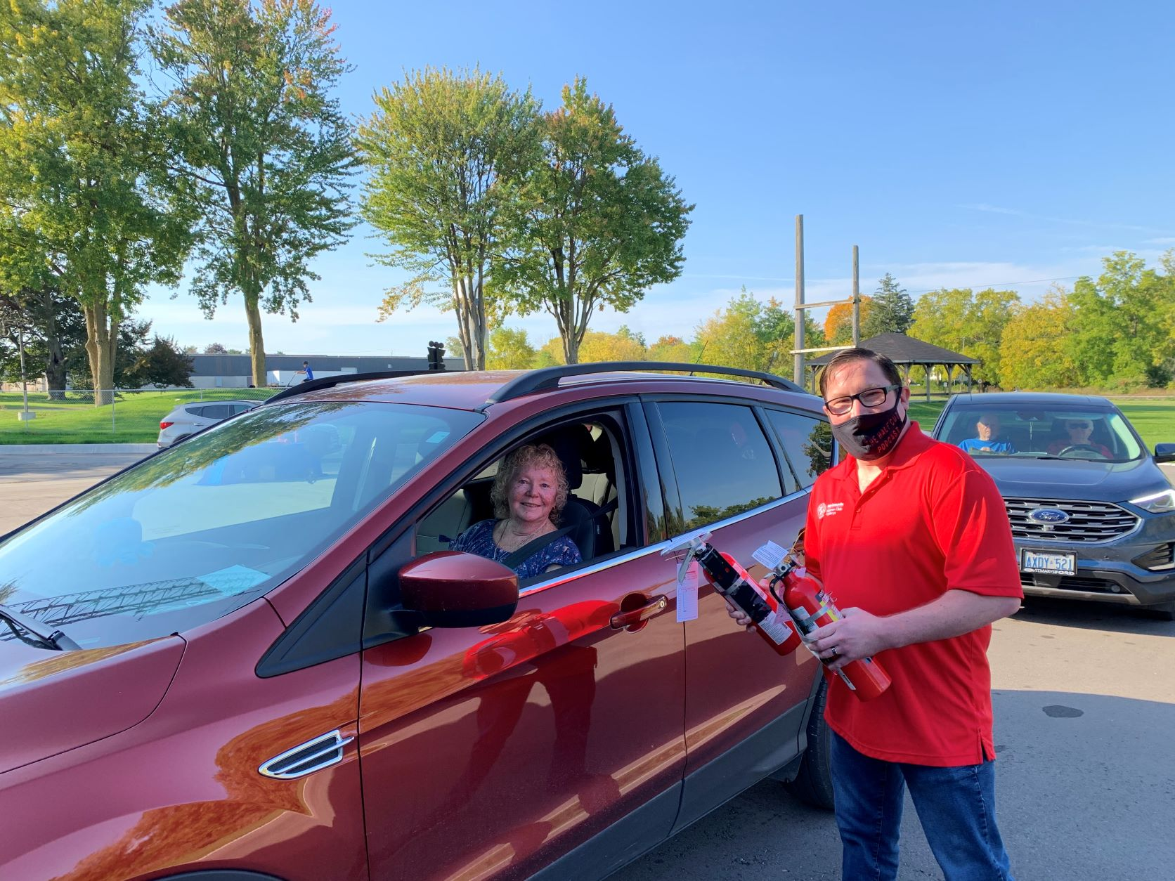 St. Marys Kinsmen Chris Swarthout hands a local resident a fire extinguisher for her vehicle at the first Cindy's Law Fire Extinguisher Giveaway on October 2, 2021.